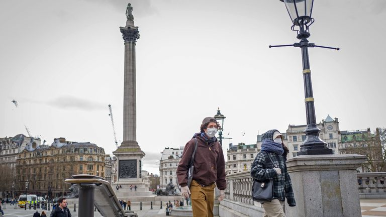 """A man and a woman wearing protective face masks leave Trafalgar Square in central London on March 15, 2020. - britain on Sunday said its criticised plan to deal with coronavirus was designed to """"protect life"""" in a """"sustainable"""" manner as it prepared to unveil """"wartime-style"""" measures to tackle the outbreak. The government has yet to implement the kind of tough measures that continental Europe has adopted, but health minister Matt Hancock said Sunday it would announce emergency powers on Tuesday, which are expected to include a ban on mass gatherings. (Photo by Tolga AKMEN / AFP) (Photo by TOLGA AKMEN/AFP via Getty Images)"""