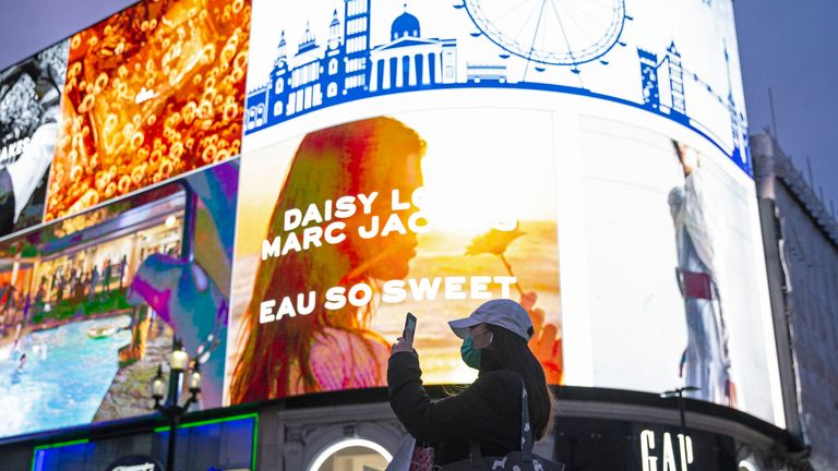 "A woman wears a mask in Piccadilly Circus, London, after the Prime Minister said that Covid-19 ""is the worst public health crisis for a generation"", and the government's top scientist warned that up to 10,000 people in the UK are already infected."