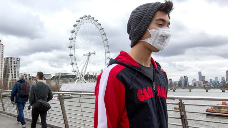 """A man in a mask on the Golden Jubilee Bridge in London, with the London Eye in the background, after the Prime Minister said that Covid-19 """"is the worst public health crisis for a generation"""", and the government's top scientist warned that up to 10,000 people in the UK are already infected."""
