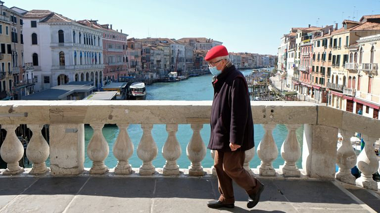 A man wearing a protective mask on an empty Rialto Bridge on Sunday with an unprecedented lockdown across of all Italy imposed to slow the outbreak of coronavirus, in Venice, Italy, March 15, 2020. REUTERS/Manuel Silvestri