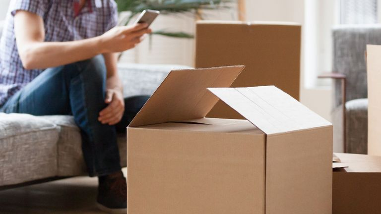 Close up carton boxes with belongings man sitting on sofa hold phone on background, wait call to delivery service moving at new house concept, banner for website header design with copy space for text