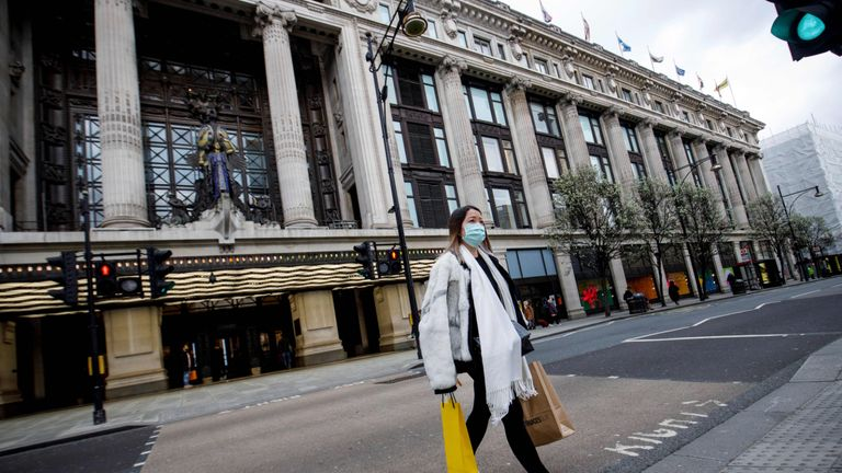A woman wears a protective face mask as she leaves from a Selfridges department store on Oxford Street in London on March 18, 2020, following the announcement that the store will temporarily close tonight, due to the coronavirus pandemic. - Selfridges on Wednesday announce the temporary closure of its four physical stores in London, Birmingham and Manchester. (Photo by Tolga AKMEN / AFP) (Photo by TOLGA AKMEN/AFP via Getty Images)