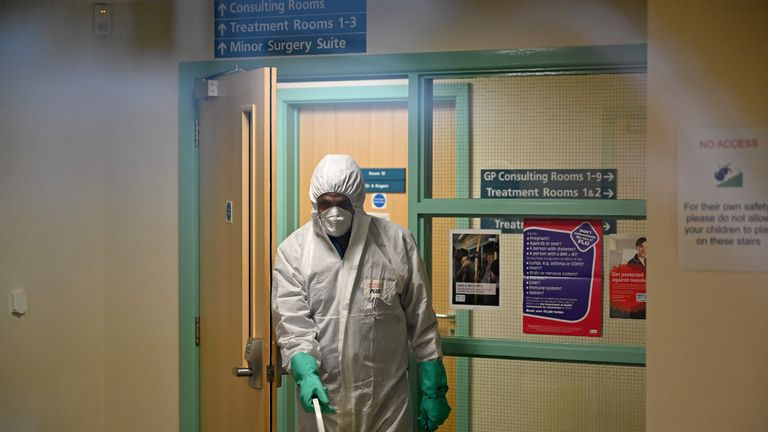"In this photograph taken through a window, a worker in protective clothing, including face mask and gloves, is pictured carrying a bucket as he works inside of at the Warmdene doctor's Surgery at County Oak Medical Centre in Brighton, southern England on February 10, 2020, after it closed for ""urgent operational health and safety reasons"", following reports a member of staff was infected with the 2019-nCoV strain of the novel coronavirus, Covid-19.. - The British government on Monday warned the outbreak of novel coronavirus was a ""serious and imminent threat"" and reported four new cases that brought the total recorded in the country to eight. Two hospitals The Royal Free and Guys and St Thomas', have both been designated as ""isolation"" facilities, with both currently housing Britons who have returned from Wuhan, the Chinese city at the centre of the outbreak. (Photo by Glyn KIRK / AFP) (Photo by GLYN KIRK/AFP via Getty Images)"