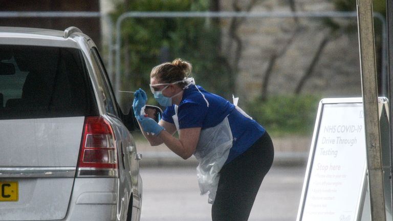 CHESSINGTON, ENGLAND - MARCH 28: A nurse is seen swabbing the occupants of a car at a drive through COVID-19 testing station at Chessington World Of Adventures Resort on March 28, 2020 in Chessington, England. Critical care nurses, GPs and ambulance drivers are among the medical workers who will be tested at similar sites across the country. The United Kingdom is nearing 20,000 confirmed COVID-19 cases and around 1,000 fatalities, and his imposed quarantine measures to slow its spread. (Photo by Peter Summers/Getty Images)