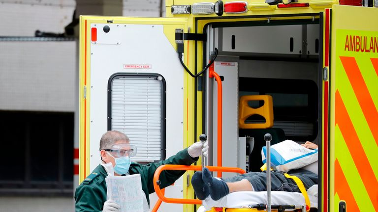A member of the ambulance services assists in moving a patient from an ambulance to St Thomas' Hospital in London on March 31, 2020, as the country is under lockdown due to the novel coronavirus COVID-19 pandemic. (Photo by Tolga AKMEN / AFP) (Photo by TOLGA AKMEN/AFP via Getty Images)