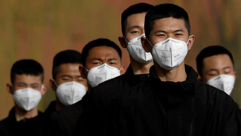 FILE PHOTO: Security personnel wearing face masks to contain the spread of coronavirus disease (COVID-19) walk along a street outside the Forbidden City in Beijing, China March 18, 2020. REUTERS/Carlos Garcia Rawlin/File Photo