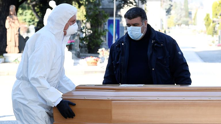 Workers transport a coffin into a cemetery