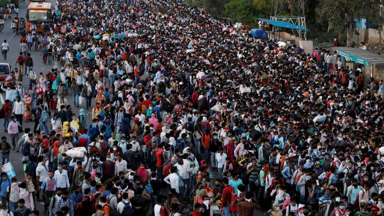 People wait to board buses in New Delhi