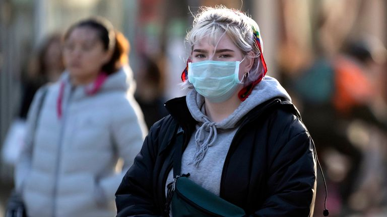 A woman wears a surgical face mask in Cardiff as three people have died from the coronavirus in the UK