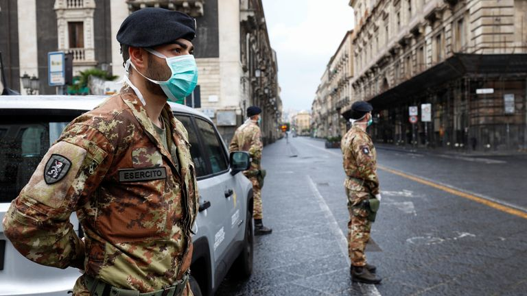 Italian soldiers wearing protective masks work at a roadblock after Italy reinforced the lockdown measures to combat the coronavirus disease (COVID-19) in Catania, Italy March 21, 2020