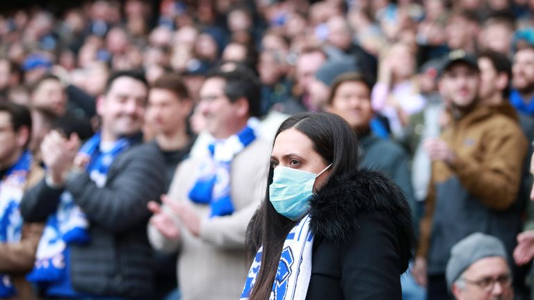 A fan in the stands wears a mask during the Premier League match at Stamford Bridge, London.