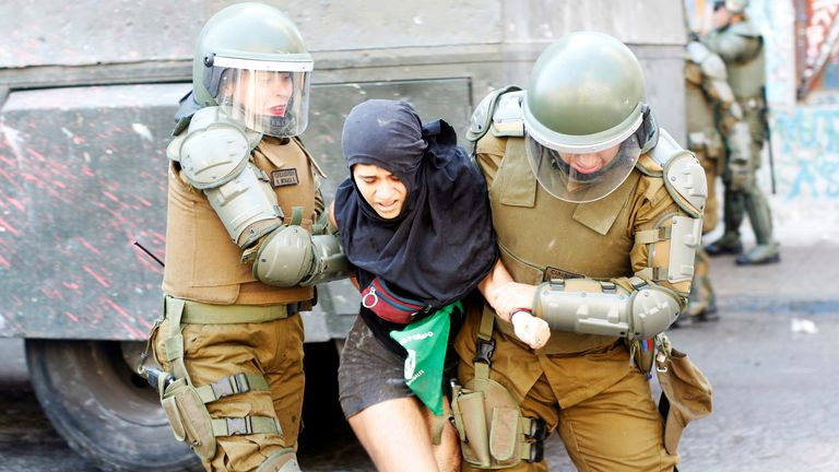 A demonstrator's detained at a rally during the International Women's Day in Santiago