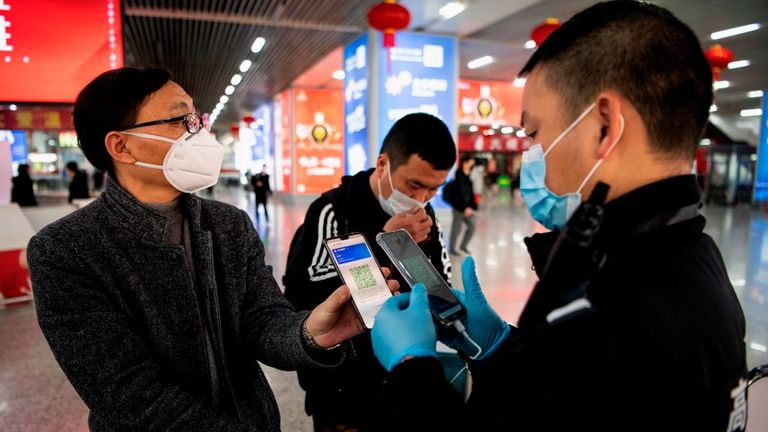This photo taken on February 28, 2020 shows a passenger wearing a face mask as he shows a green QR code on his phone to show his health status to security upon arrival at Wenzhou railway station in Wenzhou. - The National Health Commission on March 1 reported 573 new infections, bringing the total number of cases in mainland China to 79,824. (Photo by NOEL CELIS / AFP) (Photo by NOEL CELIS/AFP via Getty Images)