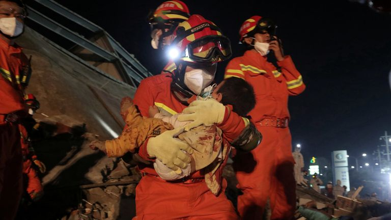A worker wearing a face mask rescues a child at the site where a hotel being used for the coronavirus quarantine collapsed, in the southeast Chinese port city of Quanzhou, Fujian province, China