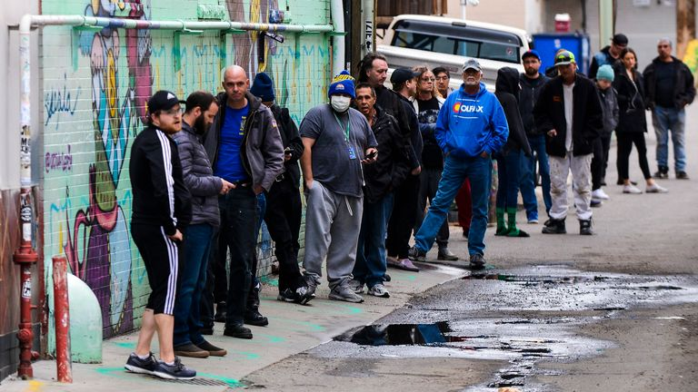 DENVER, CO - MARCH 23: People stand in freshly painted circles, six-feet-apart, as they wait in a two-hour line to buy marijuana products from Good Chemistry on March 23, 2020 in Denver, Colorado.