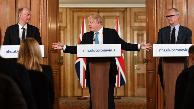 LONDON, ENGLAND - MARCH 19: Chief Medical Officer Professor Chris Whitty (L) and Chief Scientific Adviser Patrick Vallance (R) look on as British Prime Minister Boris Johnson (C) gestures