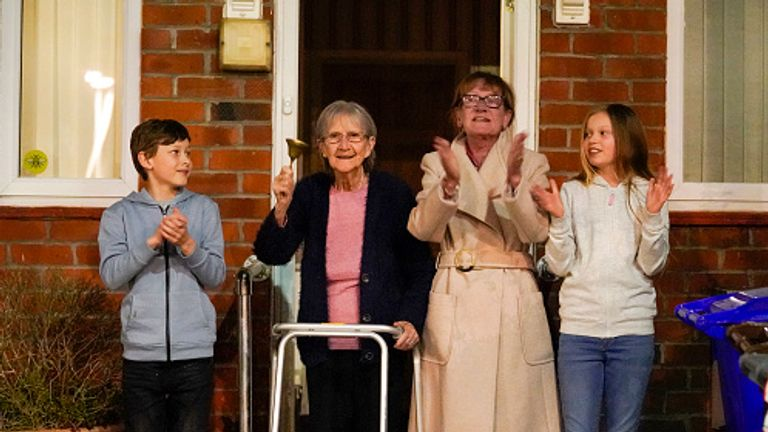 Barbara Leigh, aged 93 rings a bell for the NHS with her family - across the road from Wythenshawe Hospital in Manchester