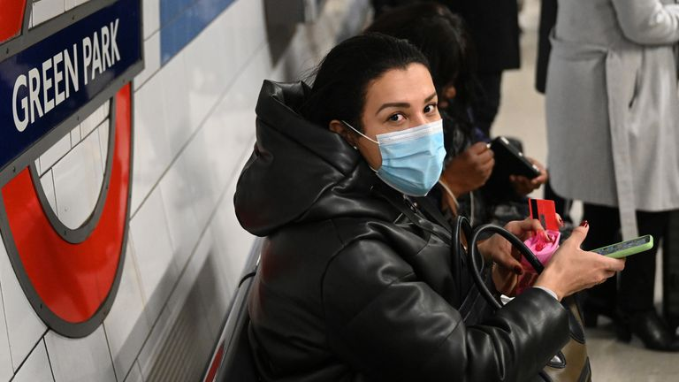 A passenger wears a surgical face mask as they use the London underground