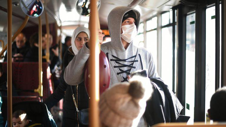 A pedestrian wears a protective facemask