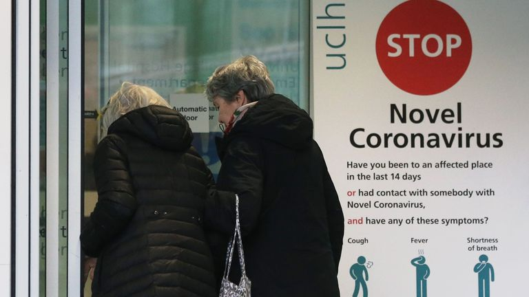 Two women walk past a sign providing guidance information about novel coronavirus (COVID-19) at one of the entrances to University College Hospital in London on March 5, 2020. - The number of confirmed cases of novel coronavirus COVID-19 in the UK rose to 85 on March 4, with fears over the outbreak delaying the global release of the new James Bond movie and causing lack of demand for air travel that has proved the final nail in the coffin for British regional airline Flybe which went into admini