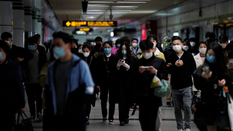 Passengers wearing face masks are seen in Shanghai after the city's emergency alert level for coronavirus was downgraded