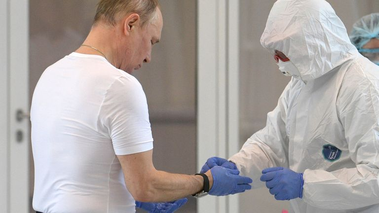 Vladimir Putin puts on protective gear as he visits a hospital near Moscow