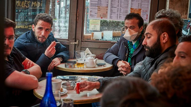 A man sits in a Paris cafe wearing a face mask as indoor gatherings of more than 5,000 were banned