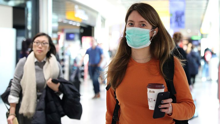 A woman wears a surgical mask as she walks through Terminal 5 at Heathrow Airport in London, Britain March 6, 2020. REUTERS/Hannah McKay