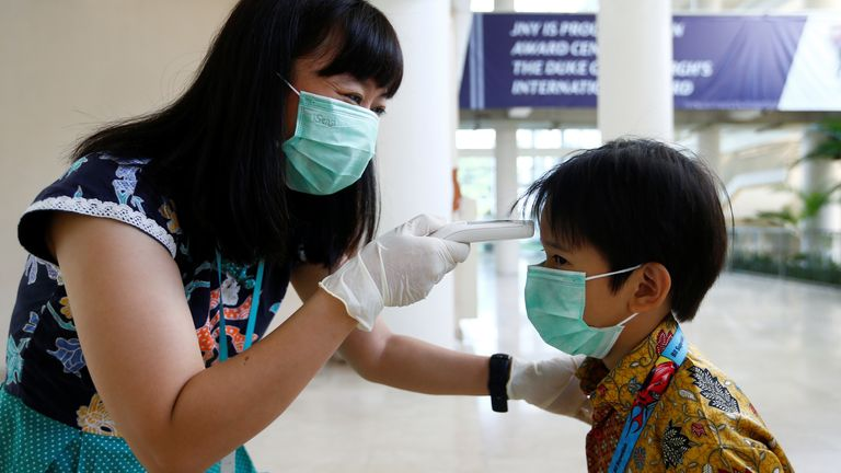 A teacher checks a student with a thermal scanner at school after Indonesia confirmed its first cases of coronavirus disease
