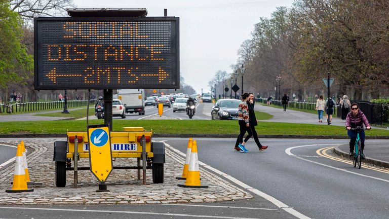 A sign notifies passers by of the 2 meter social distancing measures in place, as people exercise in Phoenix Park in Dublin, on March 25, 2020, after Ireland introduced measures to help slow the spread of the novel coronavirus