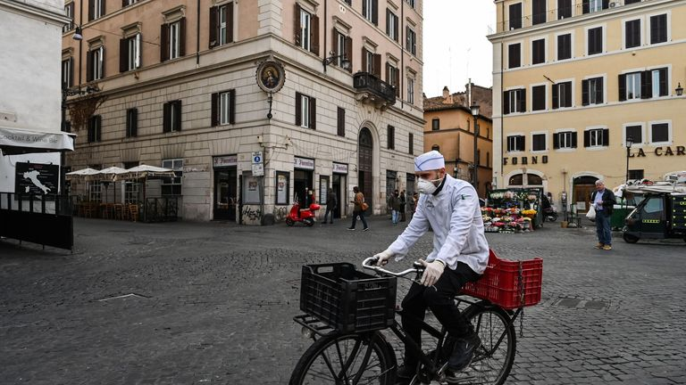 A cook wearing a respiratory mask as part of precautionary measures against the spread of the new COVID-19 coronavirus, rides a bicycle across a deserted Campo Dei Fiori square in downtown Rome on March 10, 2020 as Italy imposed unprecedented national restrictions on its 60 million people on March 10 to control the deadly coronavirus. (Photo by Alberto PIZZOLI / AFP) (Photo by ALBERTO PIZZOLI/AFP via Getty Images)
