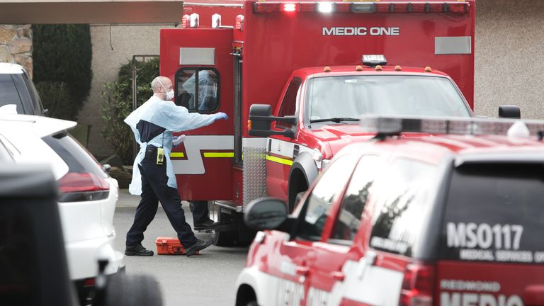 Ambulance staff prepare to transport a patient from the Life Care Center nursing home where some patients have died from COVID-19 in Kirkland, Washington on March 5, 2020