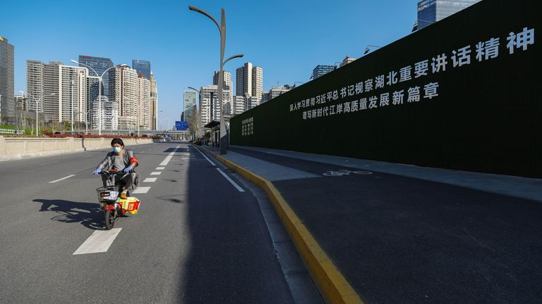 """This photo taken on March 18, 2020 shows a man wearing a mask, amid concerns over the COVID-19 coronavirus outbreak, riding past a propaganda slogan about Chinese President Xi Jinping beside a road in Wuhan, in China's central Hubei province. - The slogan reads """"Study the spirit of Secretary Xi Jinping's important speech during his inspection in Hubei, write a new chapter of the high quality development of Jiangan district in the new era"""". The slogan is a reference to Xi's visit to Wuhan, the ep"""
