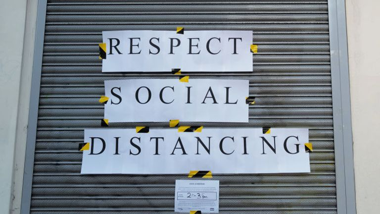 A sign urges Britons to 'respect social distancing' on a pharmacy in London