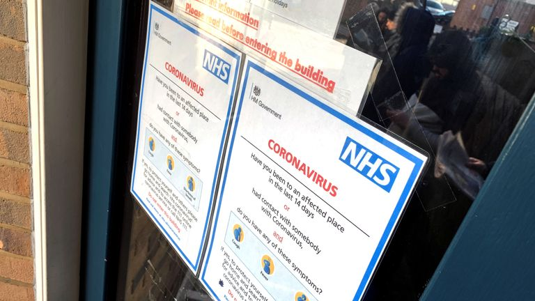People queuing to get into surgery before a clinic opens are seen reflected in the glass of a doorway behind National Heath Service (NHS) information leaflets on coronavirus in London, Britain March 13, 2020. REUTERS/Russell Boyce