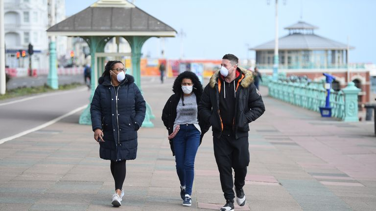 People stroll across Brighton seafront during the coronavirus outbreak