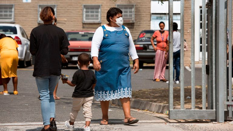 A woman wearing a protective face mask walks out walk out of the Belhar Clinic in Belhar, near Cape Town