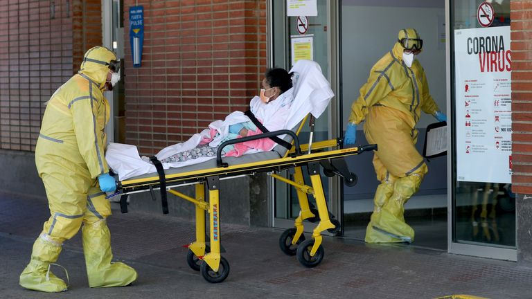 Ambulance workers in full protective gear arrive with a patient at the Severo Ochoa Hospital during the coronavirus disease (COVID-19) outbreak in Leganes, Spain, March 26, 2020. REUTERS/Susana Vera