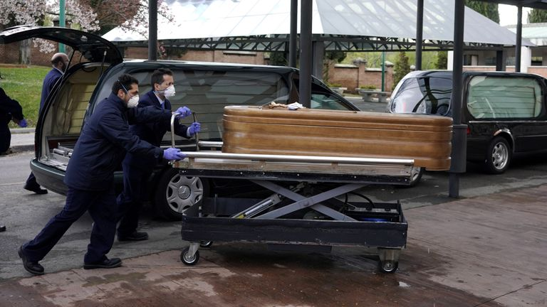 The coffin of a coronavirus victim is moved into a crematorium in Madrid