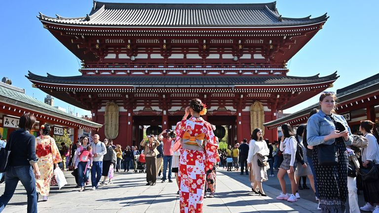 A woman wearing a kimono stands in front of a structure on the grounds of Sensoji temple in Tokyo's Asakusa district on April 16, 2019. (Photo by Charly TRIBALLEAU / AFP) (Photo credit should read CHARLY TRIBALLEAU/AFP via Getty Images)