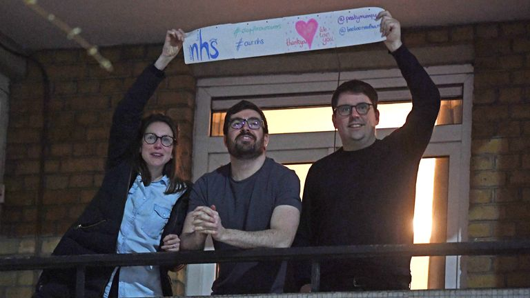 People clap from a block of flats opposite St Thomas' Hospital in London. Pic: Facundo Arrizabalaga/EPA-EFE/Shutterstock