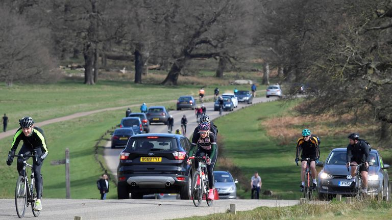 Pedestrians and vehicles are seen in Richmond Park with the City of London skyline behind, as the number of coronavirus disease cases (COVID-19) grow around the world, London, Britain