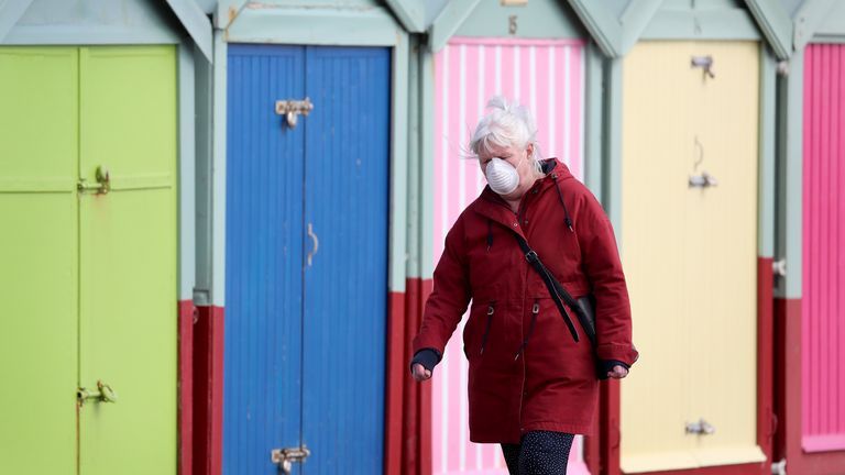 A mask-wearing woman walks along Brighton seafront during the UK coronavirus outbreak