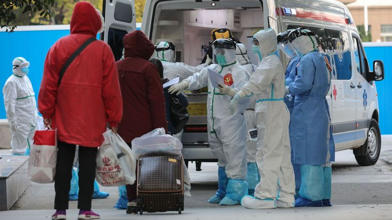 A medical staff member checks information as patients infected by the COVID-19 coronavirus leave from Wuhan No.3 Hospital to Huoshenshan Hospital in Wuhan in China's central Hubei province on March 4, 2020