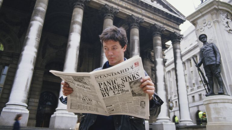 A young man reads a copy of the Evening Standard outside the Royal Exchange in London, with a headline referring to that day's stock market crash, known as Black Monday, 19th October 1987