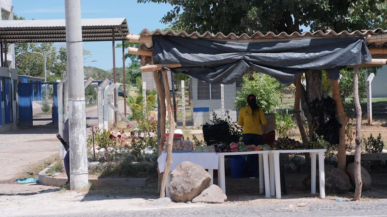 A woman inmate sells vegetables from a roadside watched by a guard