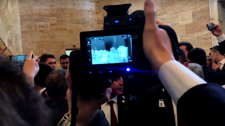 The aide scanned journalists and politicians who crowded around the Turkish leader as he arrived in parliament