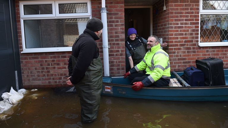 Local people go door to door using a boat collecting belongings and helping residents in the rising floodwaters in East Cowick