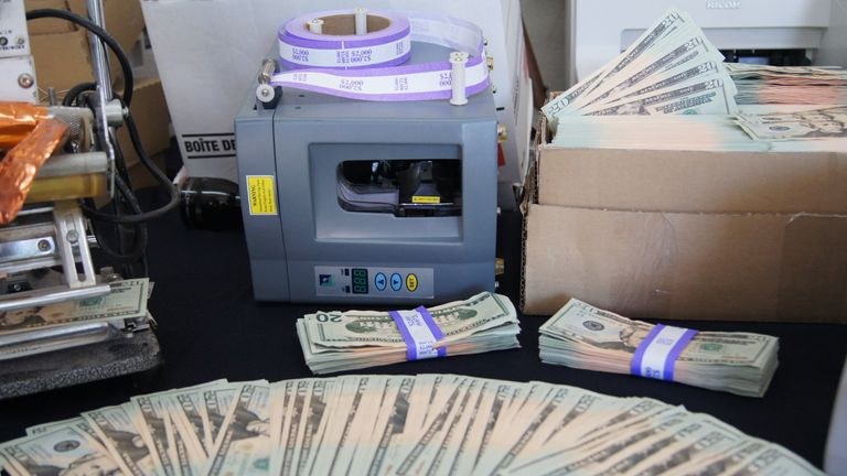 An image shows some of the counterfeit notes and equipment found by police after Bourassa's arrest. Pic: Royal Canadian Mounted Police