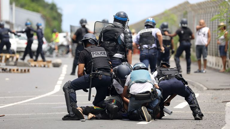 French police officers arrest a demonstrator after the Sun Princess arrived at Reunion Island